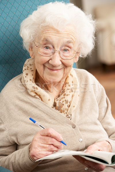 Senior Woman Relaxing In Chair At Home Completing Crossword Stock photo © monkey_business