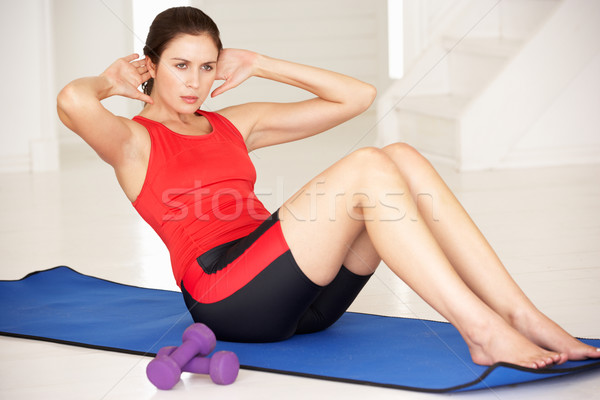 Woman doing sit-ups in home gym Stock photo © monkey_business