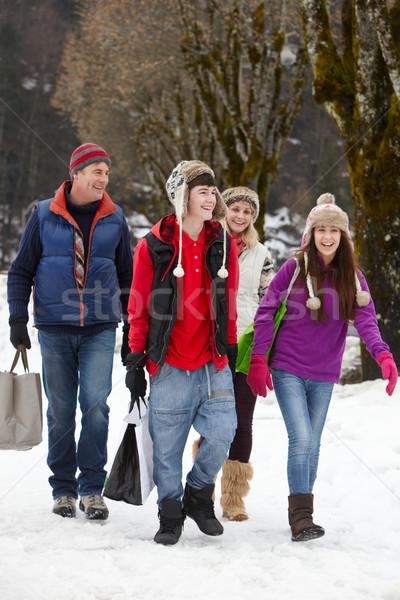 Teenage Family Carrying Shopping Walking Along Snowy Street Stock photo © monkey_business