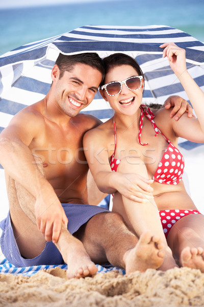 Couple Sheltering From Sun Under Beach Umbrella Stock photo © monkey_business