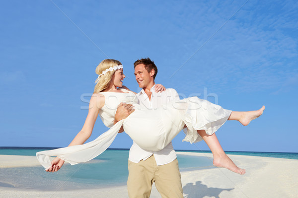 Stock photo: Groom Carrying Bride At Beautiful Beach Wedding