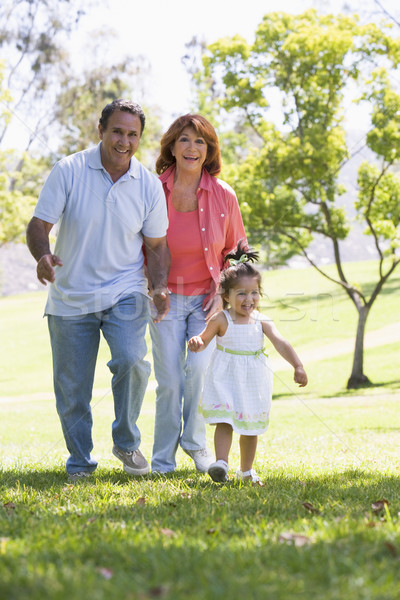 Stock photo: Grandparents walking in park with granddaughter