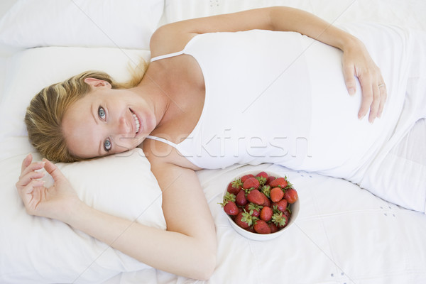 Pregnant woman lying in bed with bowl of strawberries smiling Stock photo © monkey_business