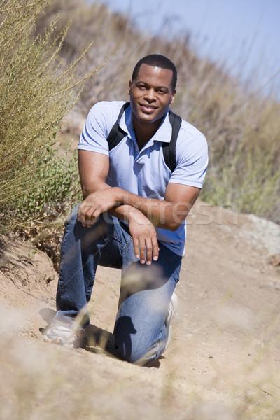 Man crouching on path to beach smiling Stock photo © monkey_business