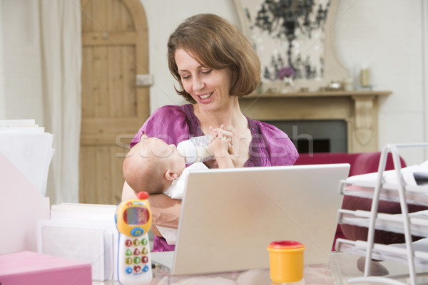 Stock photo: Mother and baby in home office with laptop