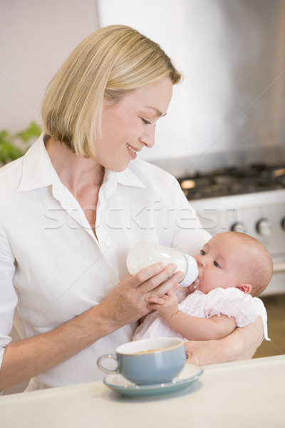 Mother feeding baby in kitchen with coffee smiling Stock photo © monkey_business