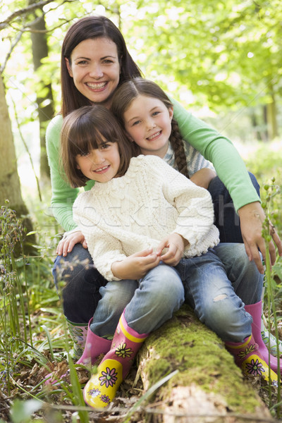 Mother and daughters outdoors in woods sitting on log smiling Stock photo © monkey_business