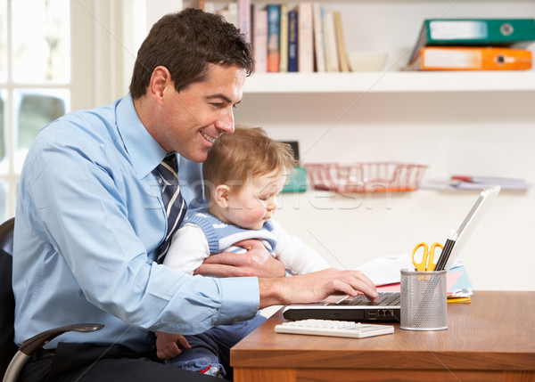 Man With Baby Working From Home Using Laptop Stock photo © monkey_business