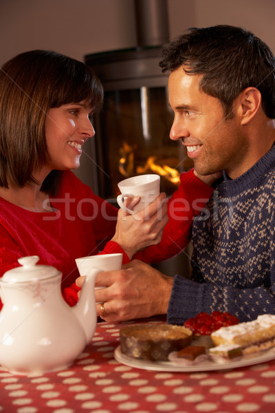 Couple Enjoying Tea And Cake By Cosy Log Fire Stock photo © monkey_business