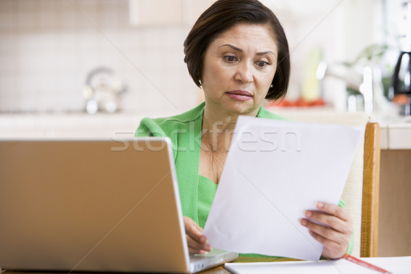 Donna cucina laptop scartoffie guardando Foto d'archivio © monkey_business