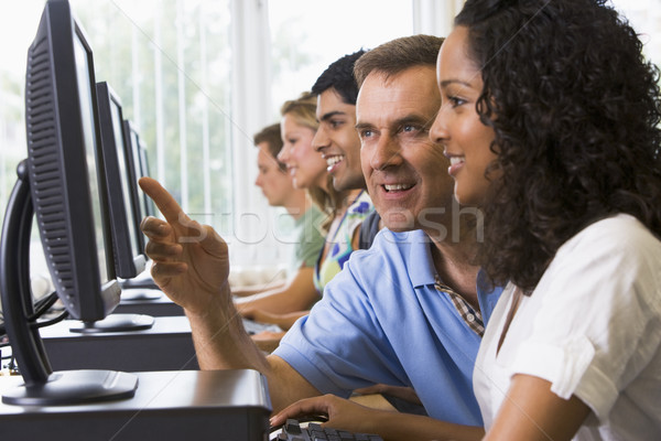 Teacher assisting college student in a computer lab Stock photo © monkey_business