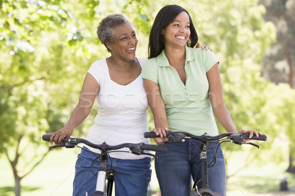 Stock photo: Two women on bikes outdoors smiling