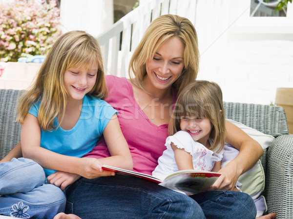 Woman and two young girls sitting on patio reading book smiling Stock photo © monkey_business