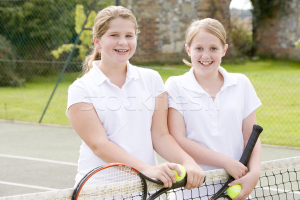Two young girl friends with rackets on tennis court smiling Stock photo © monkey_business