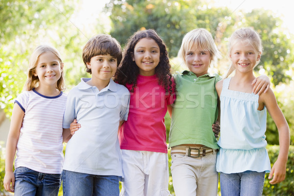 Five young friends standing outdoors smiling Stock photo © monkey_business