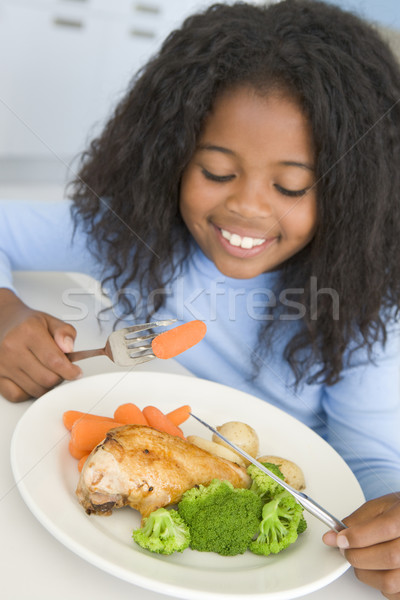 Young girl in kitchen eating chicken and vegetables smiling Stock photo © monkey_business