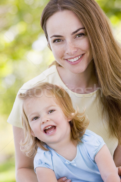 Mother holding daughter outdoors smiling Stock photo © monkey_business