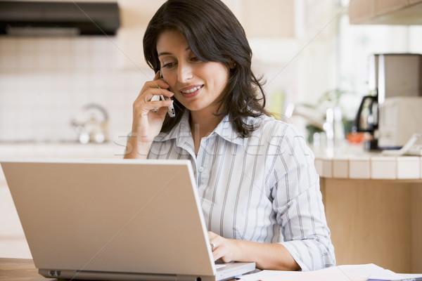 Kadın mutfak dizüstü bilgisayar cep telefonu gülümseyen kadın gülen Stok fotoğraf © monkey_business