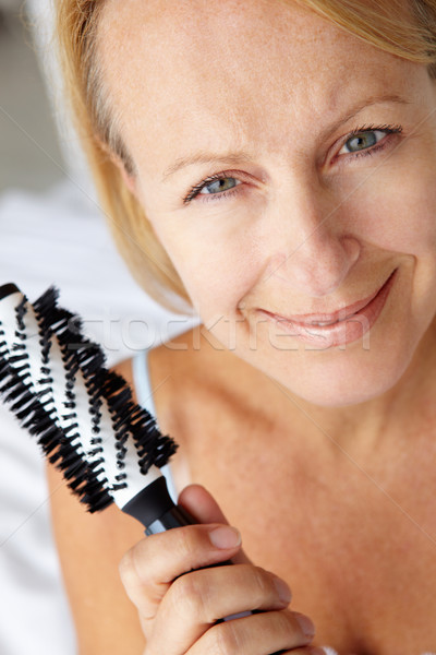 Mid age woman holding hairbrush Stock photo © monkey_business