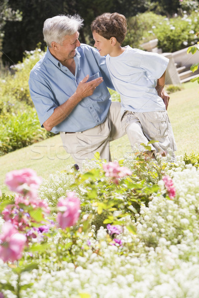 Grandfather and grandson outdoors in garden talking and smiling Stock photo © monkey_business