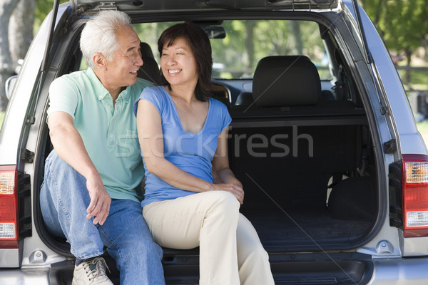 Stock photo: Couple sitting in back of van smiling