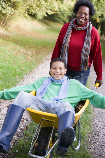 Mother pushing teenage son in wheelbarrow Stock photo © monkey_business