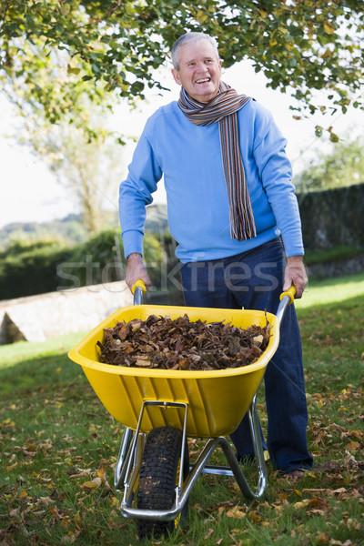 Senior man collecting autumn leaves  Stock photo © monkey_business