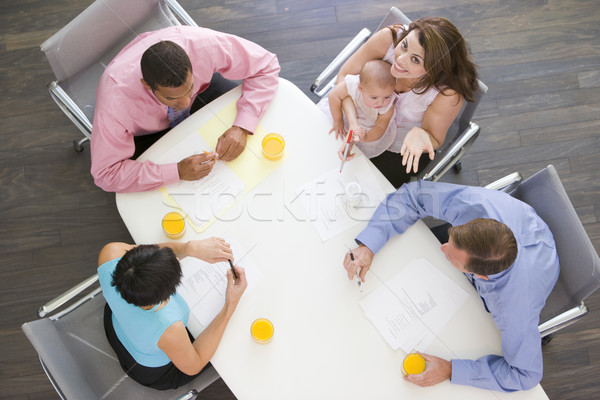 Four businesspeople in boardroom with one holding a baby smiling Stock photo © monkey_business