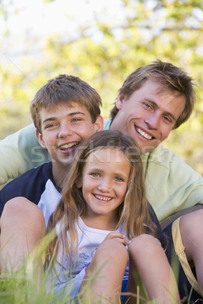 Homme deux enfants séance extérieur souriant Photo stock © monkey_business