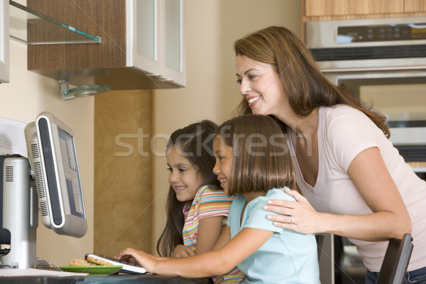 Stock photo: Woman and two young girls in kitchen with computer smiling