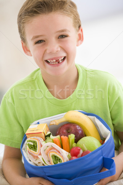 Young boy holding packed lunch in living room smiling Stock photo © monkey_business