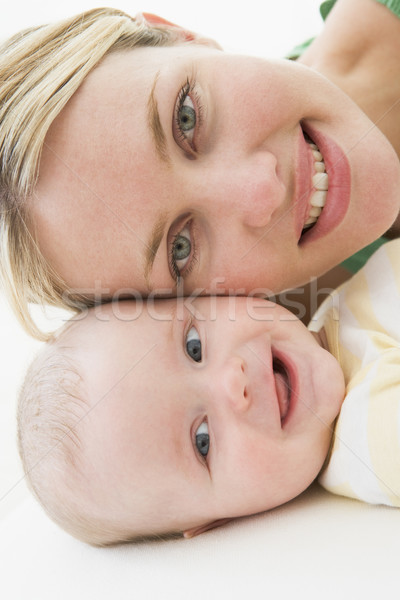 Mother and baby lying on floor smiling Stock photo © monkey_business