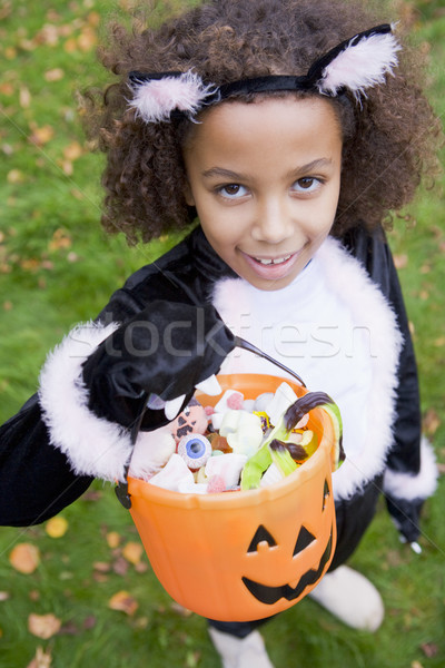 Young girl outdoors in cat costume on Halloween holding candy Stock photo © monkey_business