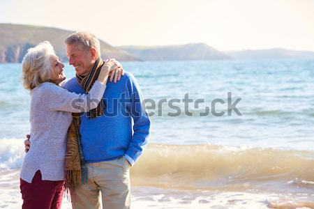 Senior Man On Holiday Kneeling On Winter Beach Stock photo © monkey_business