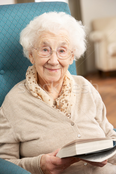 Senior Woman Relaxing In Chair At Home Reading Book Stock photo © monkey_business
