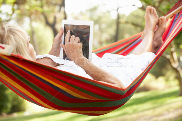 Senior Woman Relaxing In Hammock With  E-Book Stock photo © monkey_business