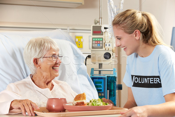 Stock photo: Teenage Volunteer Serving Senior Female Patient Meal In Hospital