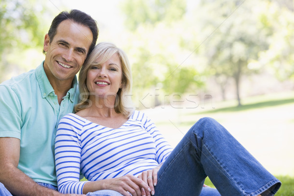 Couple relaxing outdoors in park smiling Stock photo © monkey_business