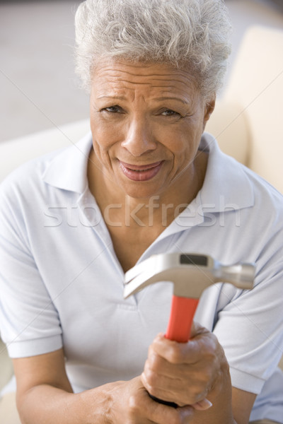 Woman holding hammer looking unsure Stock photo © monkey_business
