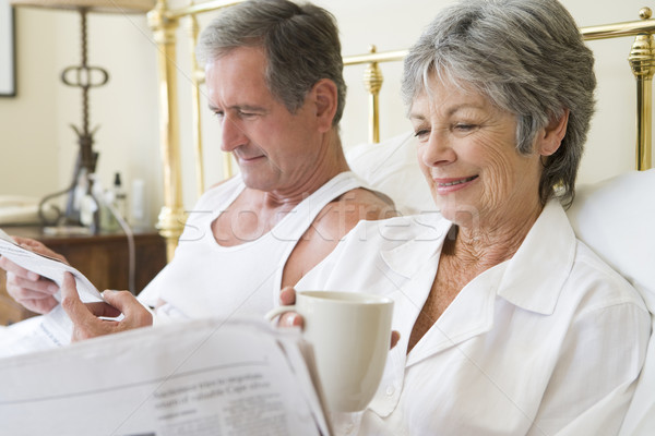 Stock photo: Couple in bedroom with coffee and newspapers smiling