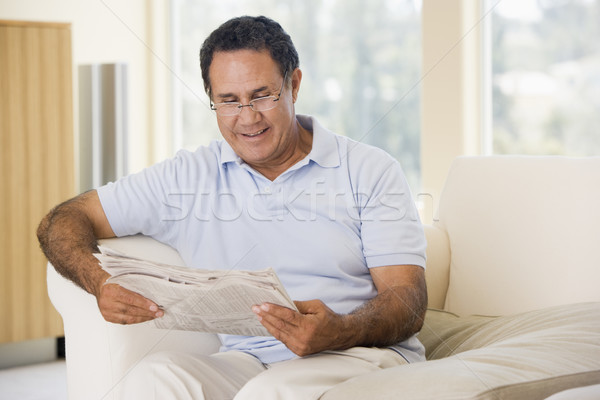 Man in living room reading newspaper smiling Stock photo © monkey_business