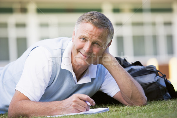 A man writing notes while lying on a campus lawn Stock photo © monkey_business