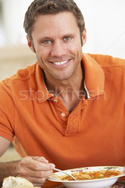 Középkorú férfi eszik leves mosolyog kamera asztal Stock fotó © monkey_business