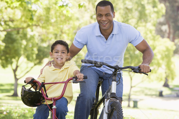 Man and young boy on bikes outdoors smiling Stock photo © monkey_business