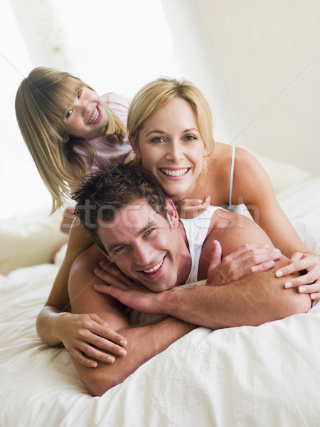Family in bed playing and smiling Stock photo © monkey_business