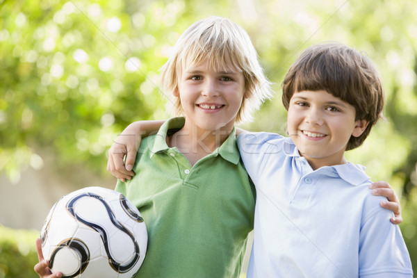 Two young boys outdoors with soccer ball smiling Stock photo © monkey_business