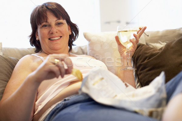 Overweight Woman Relaxing On Sofa Stock photo © monkey_business