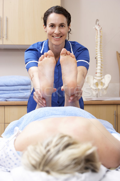 Osteopath treating female client Stock photo © monkey_business