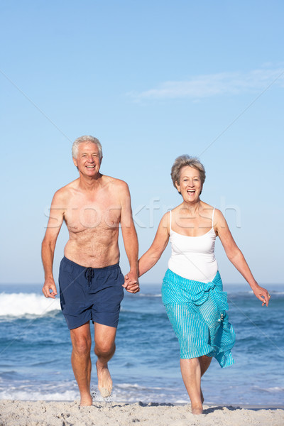 Idős pár ünnep fut homokos tengerpart nő tenger Stock fotó © monkey_business