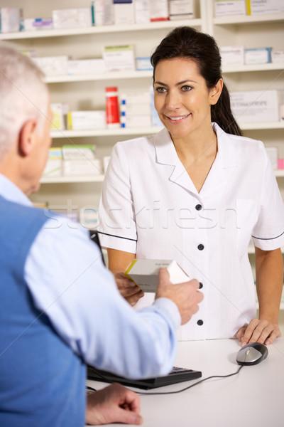 American pharmacist dispensing to senior man Stock photo © monkey_business